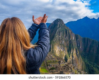 Woman with her hands open blessing Machu Picchu Incan site, over-the-shoulder shot