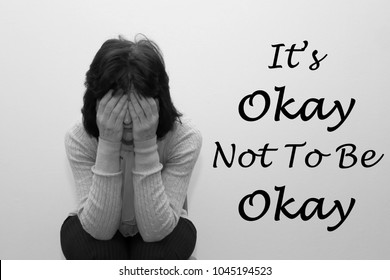 Woman with her head in her hands with the saying It's okay not to be okay written on the wall.