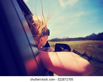 a woman with her head out the window enjoying a scenic drive through the sawtooth mountain range in idaho along an old highway toned with a retro vintage instagram filter app or action effect