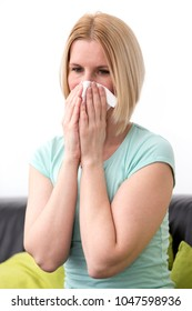 Woman in her home, blowing her nose.