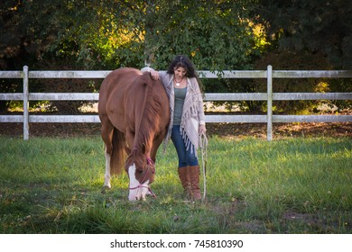 Woman and her horse in a pasture.