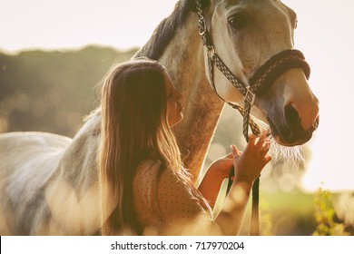 Woman with her horse at sunset, autumn outdoors scene