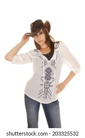 a woman in her jeans and white shirt looking at the camera in her western hat.