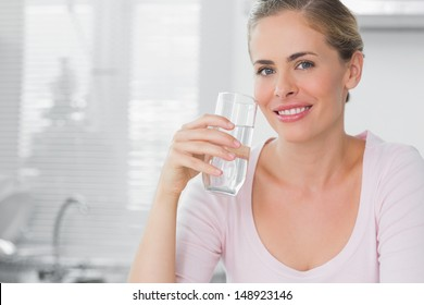 Woman in her kitchen holding glass of water