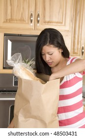 A woman in her kitchen reaching into her bag of groceries.