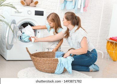 Woman and her little daughter doing laundry at home