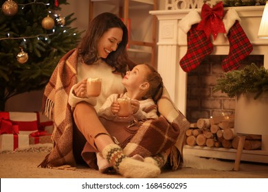 Woman and her little daughter drinking tasty cocoa at home on Christmas eve