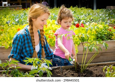 Woman with her little daughter in garden