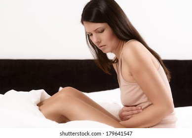 Woman with her monthly menstrual pains clutching her stomach with her hands as she becomes stressed by the ongoing cramps while sitting in her bed
