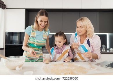 A woman and her mother are teaching their daughter to cook homemade cakes. Mother and grandmother help the girl cut round cake molds with a glass