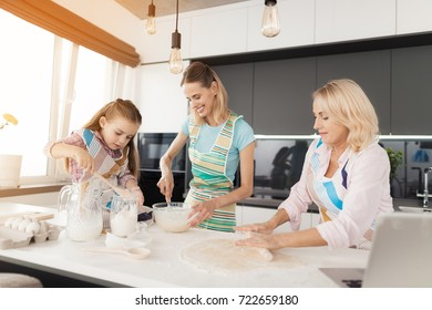 A woman and her mother are teaching their daughter to cook homemade cakes. The girl and her mother knead the dough in a glass bowl. Grandmother rolled the dough with a rolling pin