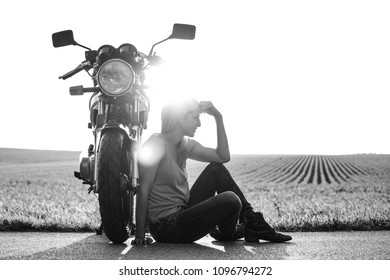 Woman and her motorcycle at sunset