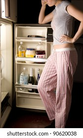 Woman in her pajamas goes into the refrigerator Late at Night Food Searching