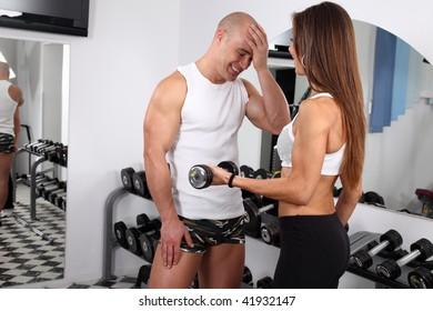 Woman with her personal fitness trainer exercising with dumbbells