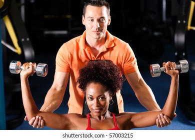 Woman with her personal fitness trainer in the gym exercising with dumbbells