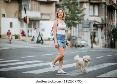 Woman and her pet dog walking trough city