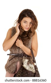 A woman with her purse hanging off of her arm full of money.