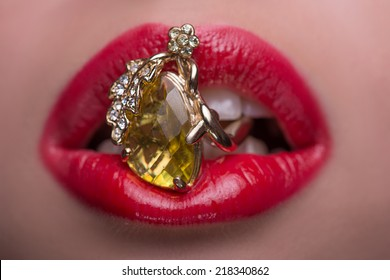 Woman with her red tempting lips holding wonderful fingering with topaz in her mouth