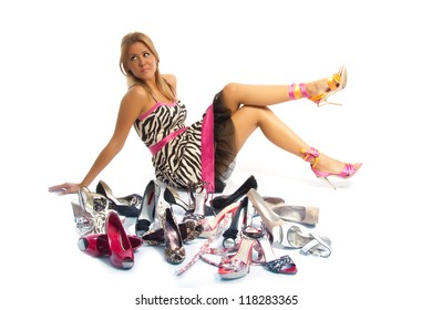 Woman and her shoes - Happy female shopaholic posing on white background behind a large selection of high heel shoes
