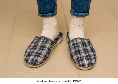 Woman with her slippers is standing on the floor