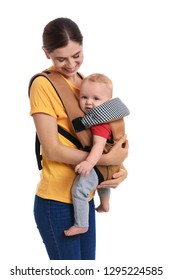 Woman with her son in baby carrier on white background