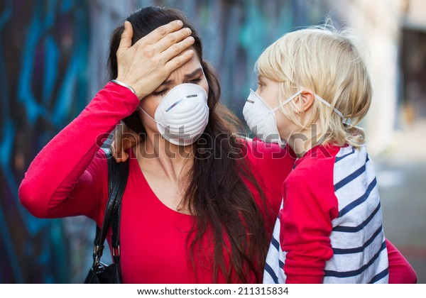 A woman and her son wearing protective face masks for pollution or virus. The woman is suffering from headache or migraine.