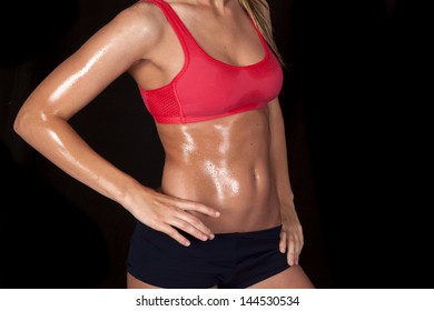 A woman in her sports bra showing off her sweaty body