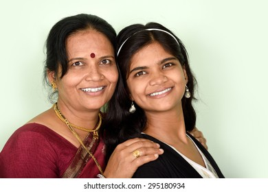 Woman and her Teenage Daughter. Close up portrait of a teenager daughter and her mother hugging and smiling