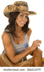 a woman in her western hat leaning on her saddle.
