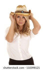a woman in her white shirt holding on to her hat with a small smile on her face.