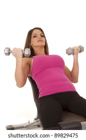 a woman in her workout outfit lifting weights.