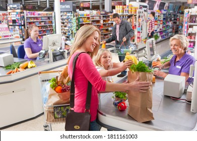 A woman with her young daughter at a checkout counter in a supermarket.