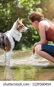 Woman and her young dog face to face on a flat river, lifestyle with the pet