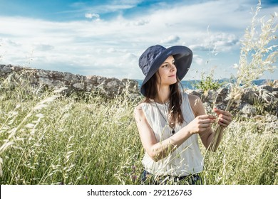Woman herbalist collecting wild herbs.
