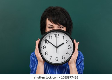 woman hides her face behind the clock, posing by chalk board, time and education concept, green background, studio shot