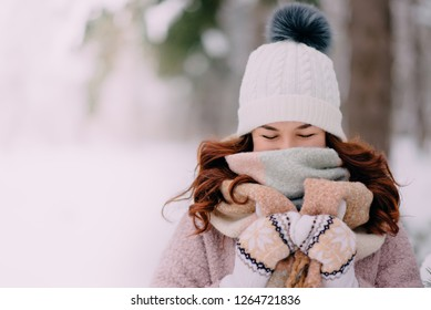 woman hides her face behind scarf because of cold