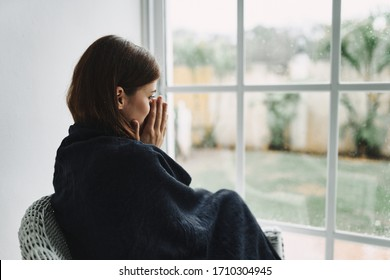 Woman hiding behind a blanket at home interior relaxation lifestyle