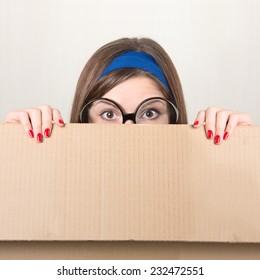 Woman hiding behind a moving box