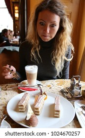 Woman hiding behind table sneaking and looking at delicious cake with sweet cream. Appetite and gluttony concept