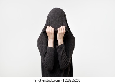 Woman hiding face under the clothes. She is oulling sweatr on her head. Depressed emotion. Wish to ba alone. Protection of personal space
