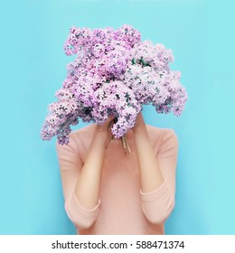 Woman hiding head bouquet lilac flowers over colorful blue background