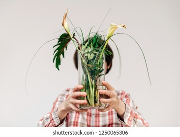 Woman hiding her face behind flower vase with two dead cala flower and multiple green leaves deadpan style against white background