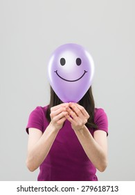 woman hiding her face behing purple balloon with smiley face drawn on it, on grey background