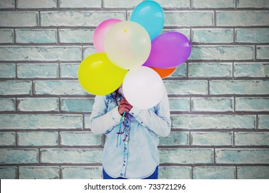 Woman hiding her face with bunch of colorful balloons  against a stone wall