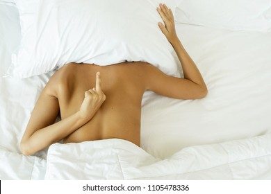 Woman hiding under the pillow and shows rude gesture like middle finger