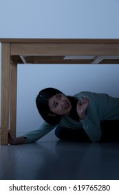 A woman hiding under the table, an earthquake, an earthquake disaster, a disaster