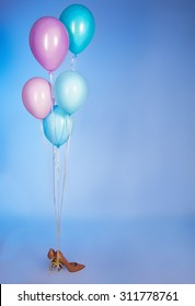 Woman  high hills shoes with balloons over bright pink background.