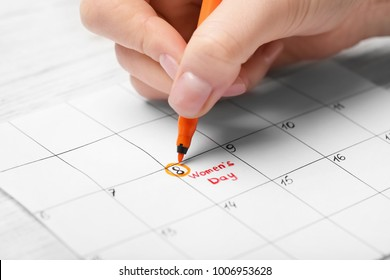 Woman highlighting date on calendar, closeup. International Women's Day celebration