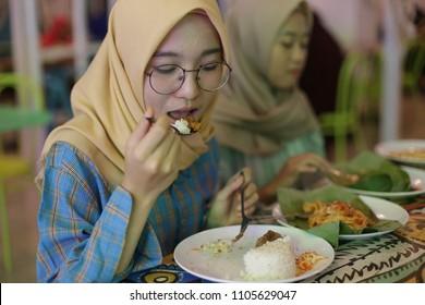 woman hijab eating food nasi lemak or nasi padang in halal restaurant. yogyakarta indonesia. june 05, 2018