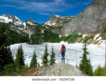 A Woman Hiker Admires Frozen Thorton Lake and Trappers Peak.  North Cascades National Park, Washington